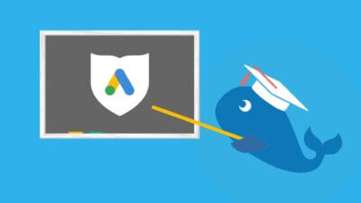 Moby the Whale in a mortarboard pointing at a chalkboard with the Google Ad Grant symbol on it